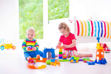 play blocks: Two happy children playing with toy cars, cute curly toddler girl and a funny baby boy, brosther and sister, sitting on the floor building blocks in a sunny white bedroom with big window