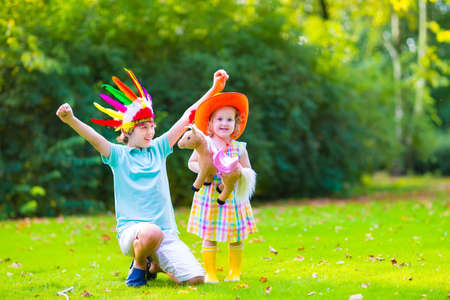 Two happy kids, laughing boy dressed as native American with colorful feather hat and little curly toddler girl in yellow boots with a toy horse playing cowboy outdoors on a sunny summer day