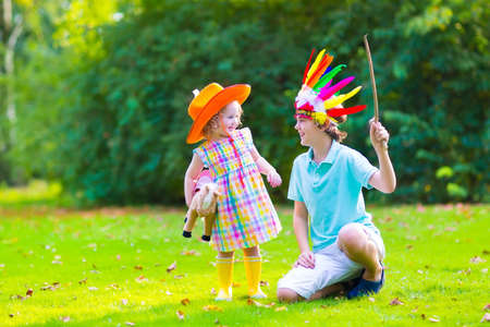 Two happy kids, laughing boy dressed as native American with colorful feather hat and little curly toddler girl in yellow boots with a toy horse playing cowboy outdoors on a sunny summer day Stock Photo