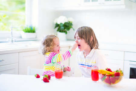 healthy meals: Happy teenager boy and his cute toddler sister having fruit for breakfast before school and kindergarten drinking juice in a sunny white kitchen with a window Stock Photo