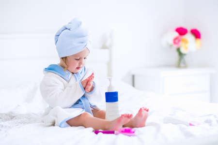 彼女濡れた髪立地の日当たりの良い寝室にシャワーまたは入浴の後にタオルで白と青のバスローブでかわいい巻き毛の小さな女の子 写真素材