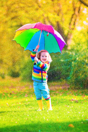 Funny cute curly toddler girl wearing yellow waterproof coat and boots holding colorful umbrella playing in the garden by rain and sun weather on a warm autumn or summer day photo