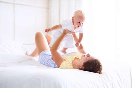幸せな若い母親は、彼女のかわいい赤ちゃん、モダンな家の寝室で晴れた朝を楽しむ白いベッドで遊ぶかわいい金髪の巻き毛少年を保持