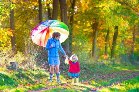 lluvia paraguas: Feliz madre joven y su adorable hija del ni�o, ni�a rizado lindo en un vestido de colores y abrigo, jugando juntos en un hermoso parque de oto�o disfrutando de un d�a soleado de oto�o al aire libre Foto de archivo
