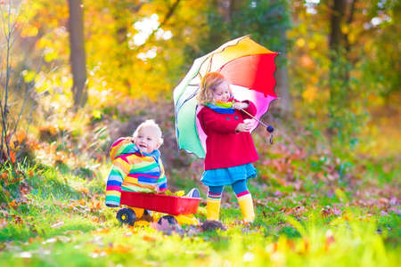 Cute little children, adorable toddler girl and a funny baby boy, brother and sister, playing in a sunny autumn park with a wheel barrow and colorful umbrella photo