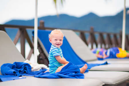 Cute happy baby boy relaxing at pool side in a beautiful tropical resort photo