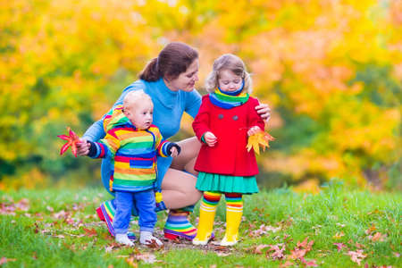 Young happy mother playing with her children, cute baby boy and adorable toddler girl wearing colorful rainbow jackets, having fun in a beautiful autumn park with yellow maple trees photo