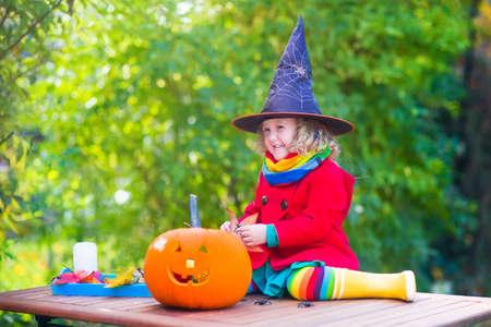 carving pumpkin: Divertida ni�a linda con sombrero y vestido colorido juego en el jard�n de oto�o que se divierte en Halloween y tallado de calabazas