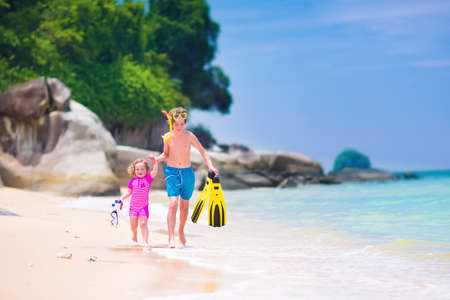 tropical island: Two happy children, teenager boy and a little toddler girl, brother and sister, running on a beautiful tropical beach after snorkeling in the ocean having fun during summer vacation Stock Photo