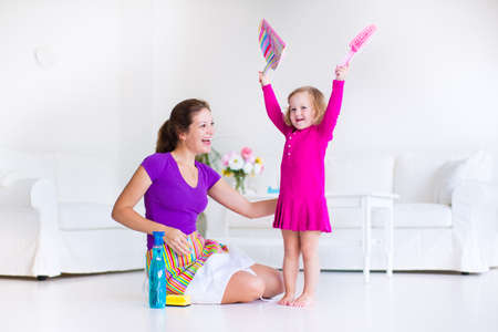Young happy mother and her little daughter, cute toddler girl, cleaning the house together sweeping the floor in a white sunny living room with modern interion and big white couch Archivio Fotografico
