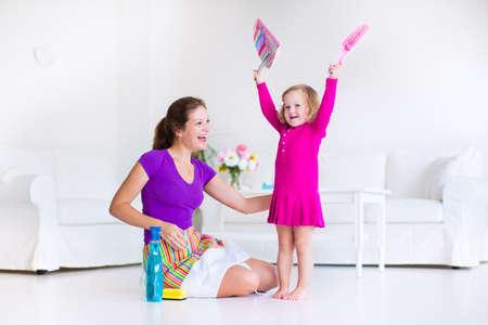 gospodarstwo domowe: Młoda matka i jej córeczka, cute girl maluch, sprzątanie domu razem zamiatanie podłogi w biały słoneczny salon z nowoczesnym interion i dużej białej kanapie