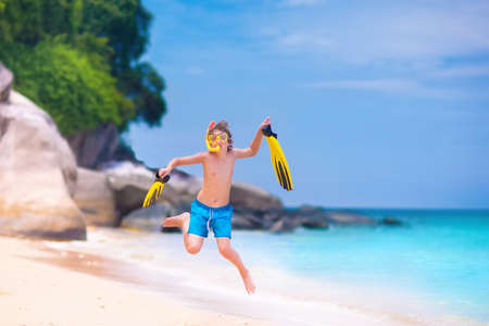 flippers: Happy little boy excited about snorkeling trip running on the beach jumping high holding his flippers and mask having fun during summer vacation on a beautiful tropical island