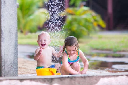 Two happy children, adorable baby boy and a little toddler girl in swimming suits playing in an outdoor shower in a tropical reaost during summer vacation photo