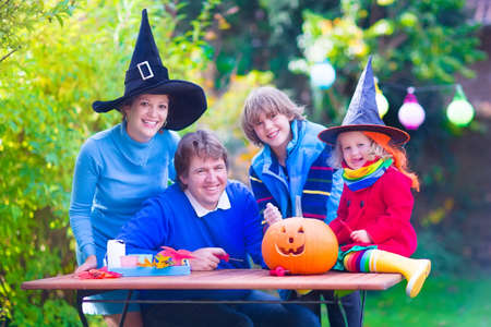 Happy young familly, parents with two children, teenager boy and funny toddler girl wearing witch costume and hat celebrating Halloween and pumpking carving in the garden photo