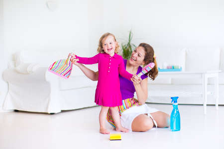 mujer limpiando: Joven madre feliz y su peque�a hija, muchacha linda del ni�o, la limpieza de la casa junto barrer el piso en una soleada sala de estar blanca con interion moderno y gran sof� blanco Foto de archivo