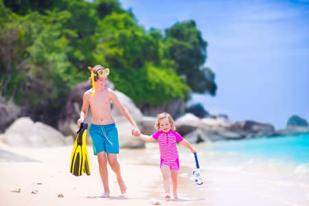 Two happy children, teenager boy and a little toddler girl, brother and sister, running on a beautiful tropical beach after snorkeling in the ocean having fun during summer vacation photo