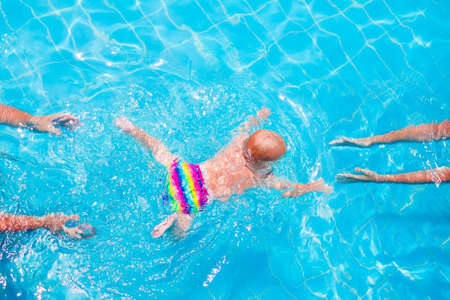 Cute little baby swimming underwater from mother to father in a pool, learning to swim lessons and early development concept