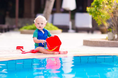 beach toys: Cute baby boy playing with red toy bucket at swimming pool in a tropical resort