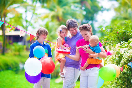 Happy big family with three children, teenager boy, cute curly toddler girl and a little funny baby celebrating birthday party woth cake and balloons outdoors in a beautiful tropical garden with palm trees photo