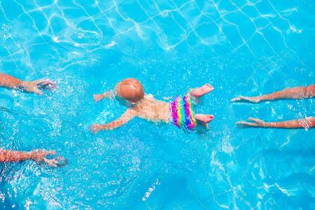 Cute little baby nuoto subacqueo dalla madre al padre in una piscina, imparare a nuotare lezioni e concetto di sviluppo precoce Archivio Fotografico - 33134608