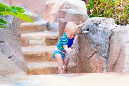 Adorable blond curly baby boy in a sun protection shirt and swimming diaper playinf with water tap at pool side on a hot summer day photo