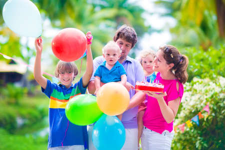Happy big family, young parents with three children, teenager boy, little toddler girl and adorable baby celebrating birthday party with strawberry cake and balloons in a sunny summer tropical garden photo