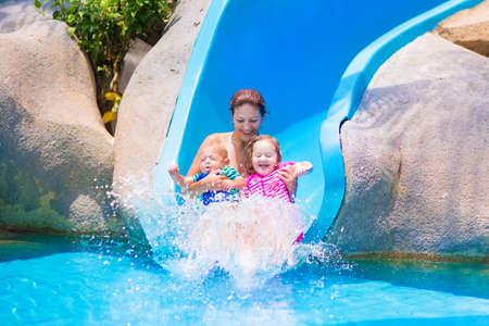 뜨거운 여름 날에 열대 수영장에서 물 sllide에서 재미 젊은 행복 어머니와 두 아이, 아기와 유아 소녀