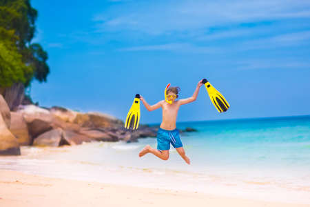 Happy little boy jumping on a beautiful tropical beach enjoying snorkeling on a exotic island during summer vacation photo