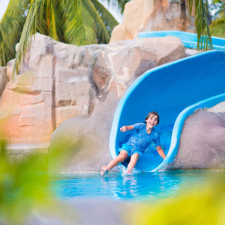 Happy boy on water slide in a swimming pool having fun during summer vacation in a beautiful tropical resort
