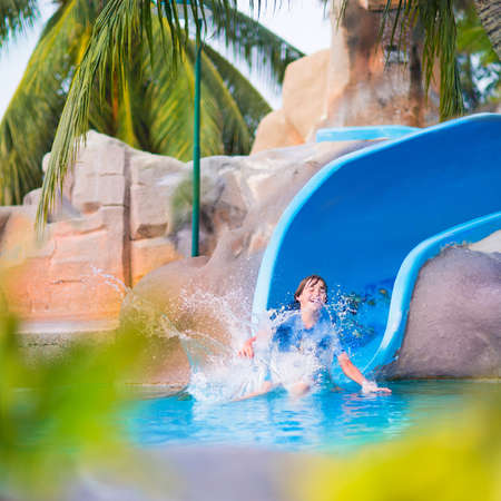 WATER SLIDE: Happy boy on water slide in a swimming pool having fun during summer vacation in a beautiful tropical resort