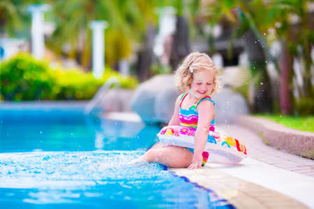 swimming suit: Adorable little girl with curly hair wearing a colorful swimming suit playing with water splashes at beautiful pool in a tropical resort having fun during family summer vacation Stock Photo