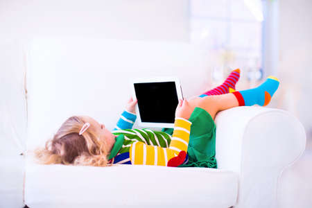 copy room: Funny little toddler girl with tablet pc relaxing on a white couch