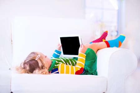 Grappige kleine peuter meisje met tablet pc ontspannen op een witte bank