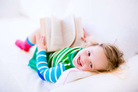 early childhood: Happy laughing little girl reading a book relaxing on a white couch at home