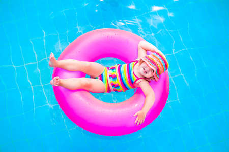 Cute funny little toddler girl in a colorful swimming suit and hat relaxing on an inflatable toy ring floating in a pool having fun during summer vacation in a tropical resort