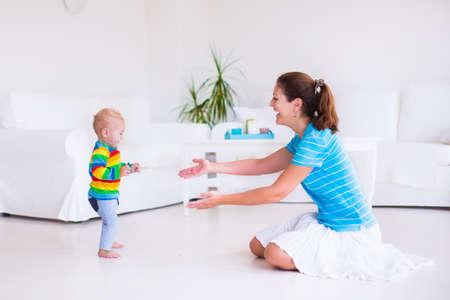 Nettes kleines Baby macht seine ersten Schritte, zu Fuß zu seiner Mutter in einem weißen sonnigen Wohnzimmer
