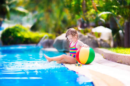 pool balls: Adorable little girl with curly hair wearing a colorful swimming suit playing with water splashes at beautiful pool in a tropical resort having fun during family summer vacation Stock Photo