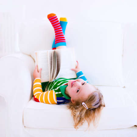 laughing girl: Happy laughing little girl reading a book relaxing on a white couch at home
