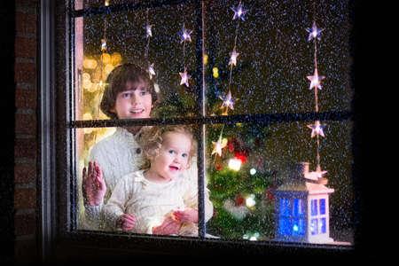 familia cenando: Dos ni�os felices, ni�a ni�o rizado y riendo ni�o en su�teres de invierno de punto caliente de pie junto a una ventana en una sala de estar decorada con �rboles de Navidad, visi�n desde fuera de la casa