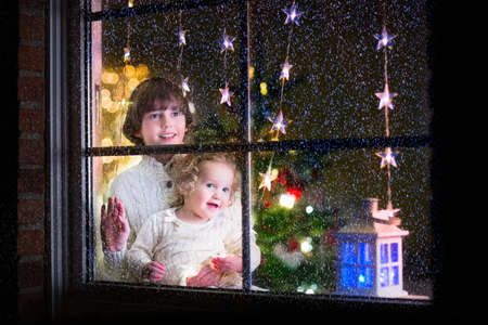 new home: Two happy children, little curly toddler girl and laughing boy in warm knitted winter sweaters standing next to a window in a decorated living room with Christmas tree, view from outside of the house