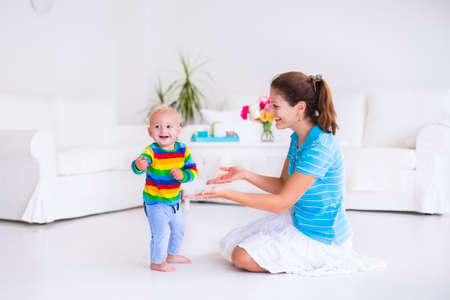 Leuk weinig babyjongen die zijn eerste stappen, lopen naar zijn moeder in een witte zonnige woonkamer Stockfoto
