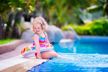 Adorable little girl with curly hair wearing a colorful swimming suit playing with water splashes at beautiful pool in a tropical resort having fun during family summer vacation Stock Photo