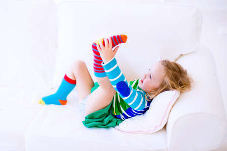 Funny little girl trying to put on warm socks on a white couch at home