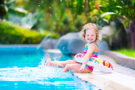 child swimsuit: Adorable little girl with curly hair wearing a colorful swimming suit playing with water splashes at beautiful pool in a tropical resort having fun during family summer vacation Stock Photo