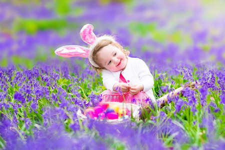 Adorable toddler girl with bunny ears having fun at Easter egg hunt in a beautiful forest with first spring flowers