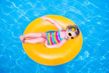 traje de bano: Ni�a ni�o divertido lindo en un traje de ba�o y sol coloridas gafas de relax en un anillo de juguete inflable flota en una piscina se divierten durante las vacaciones de verano en un resort tropical Foto de archivo