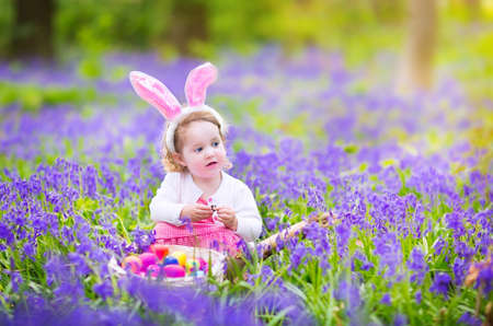 Adorable toddler girl with bunny ears having fun at Easter egg hunt in a beautiful forest with first spring flowers photo