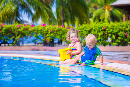 Happy baby boy and little curly toddler girl, brother and sister, playing with toy buckets and plastic shovel next to a swimming pool in a tropical resort with palm trees