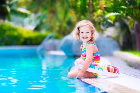splash pool: Adorable little girl with curly hair wearing a colorful swimming suit playing with water splashes at beautiful pool in a tropical resort having fun during family summer vacation Stock Photo