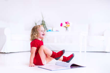 little girl sitting: Cute little girl with curly hair wearing a warm knitted red dress and socks reading a book sitting on the floor in a white living room Stock Photo